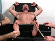 Hunk on the bondage device receives tickling from two guys