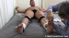 Muscle man strapped down for tickling torment session
