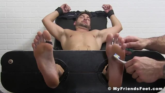Ticklish muscular jock has toothbrushes tickling his feet