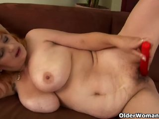 Redheaded granny with big tits is dildoing