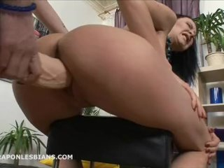 Ninel is bent over with a huge strapon dildo