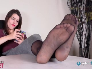 Brunette in nylons ignores you while putting her feet in your face